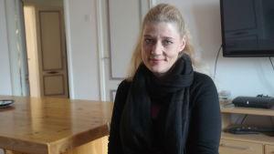 Skyddshusets direktör Marina Stobb sitter vid ett bord