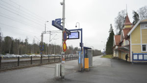 En perrong på en tågstation. Det är en mulen höstdag. En man står vid en byggnad på stationen.