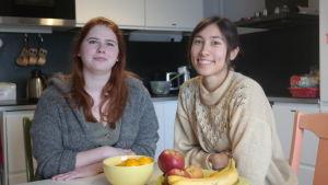 Volontärerna Ida Tiirikainen och Johanna Aintila sitter vid köksbordet i De ungas skyddshus i Åbo