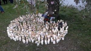 Ljus till åminnelse av en död flykting från Afghanistan vid Nykarleby älv.