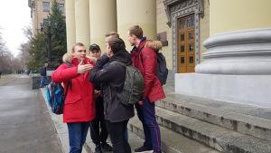 En grupp studerande står och diskuterar på trappan till en byggnad.