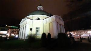 Åbo ortodoxa kyrka lyses upp av starka strålkastare en sen höstkväll. I bakgrunden ses staketet mot torgparkeringsbygget.