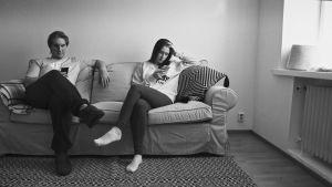Nuori mies ja nainen istuvat sohvalla ja katsovat kännyköitään.