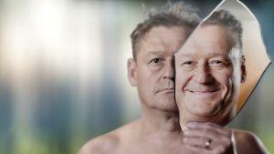 Mies käsitellyssä kuvassa, jossa hänen toinen naamansa on vakava, toinen hymyilee.