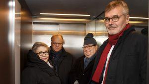 Fyra personer står inklämda i en hiss.