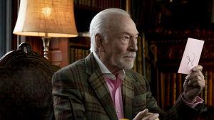 Harlan Thrombey (Christopher Plummer) sitter vid sitt skrivbord och ser allvarlig ut samtidigt som han håller ett ljusrött kuvert i sin hand.