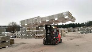 En röd truck transporterar element ute på ett stort fabriksområde.