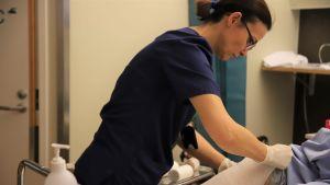 Sairaanhoitaja Edita Mullo laittaa potilaalle tukisukkaa jalkaan.