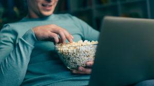 Man tittar på film på laptop och äter popcorn