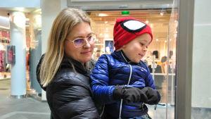 Petra Vähämaa håller sin son i famnen och tittar på någonting.