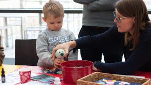 BUU-dagen i Hfors 2019. Mamma hjälper sin son att stämpla ett papper med BUU-stämpeln.