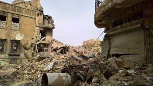 Sodan raunioittama Aleppo maaliskuussa 2017, talojen raunioita ja hiekkasäkkejä ikkuna-aukoissa.