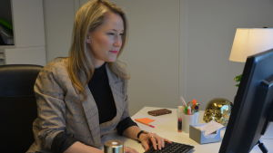 Ung kvinna i kavaj vid dator.