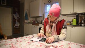 Luomutilallinen Jaana Rajakangas laskee keittiön päydän ääressä suoramyyntiasiakkaiden ostosten hintoja.