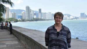 Minna Vilkuna står vid en strandpromenad framför havet. I bakgrunden höjer sig skyskrapor.