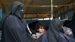 Två kvinnor klädda i svart burka och ett litet barn.