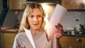 Liv (Josefin Sonck) håller i ett brev som hon bränner upp.