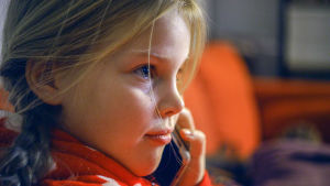 Närbild på Alma (Stella Miettinen) som ringer med sin mobil.