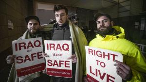 """Tre män står utomhus, det här mörkt. De ser in i kameran.De håller i lappar med slagorden """"Irak är inte säkert"""" och """"Rätt till liv""""."""