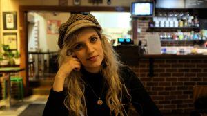 nuori nainen istuu kahvilassa