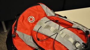 En röd och grå ryggsäck med Röda korsets logotyp.