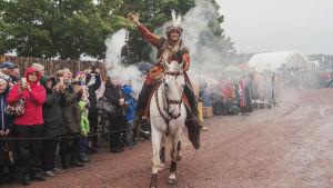 Keskiaikaiseen asuun pukeutunut nainen kantaa savuavaa lyhtyä valkoisen hevosen selässä. Taustalla yleisöä vesisateessa.