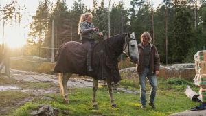 Nainen istuu hevosen selässä, jolle on laitettu loimi päälle. Mies seisoo vieressä.