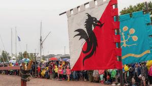 Kaksi keskiaikaista lippua ritaritunnuksineen telineessä, taustalla turnajaisareena ja yleisöä sen reunoilla.