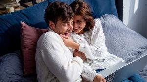 Ett ungt par halvligger i en säng med en dator i famnen och kittlar varandra.