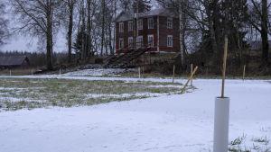 I förgrunden syns en träningsbana för hästar, i bakgrunden ett rött gammalt hus.