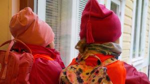 Barn ser ut genom fönstret