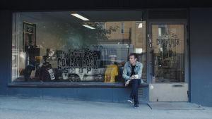 Jani Koskinen istuu Combat Rock -levykaupan edessä ulkona. Kuva dokumenttielokuvasta.