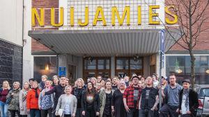 Ihmisjoukko seisoo rakennuksen edustalla, ylhäällä on kyltti, jossa lukee 'Nuijamies'.