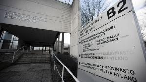 """En skylt som det står """"Esbo rättshus"""" på. I bakgrunden syns en modern byggnad."""