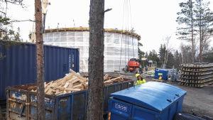 Ett vattentorn intäckt i vitt plast. I framgrunden ser man en man som jobbar med att bygga tornet.