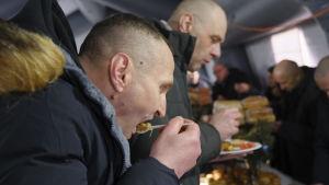 Ukrainska fångar som frigivits av proryska separatister bjöds på mat strax efter att de fått lämna gränsposteringen.