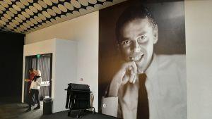 Foto på Birger Carlstedt, en ung man med stort leende, på en utställning på Amos Rex.