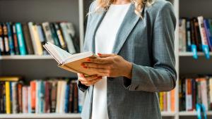 Kvinna håller i öppen bok i bibliotek