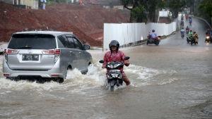 Bilar med hjulen under vatten i Indonesiens huvudstad Jakarta som drabbas av svåra översvämningar.
