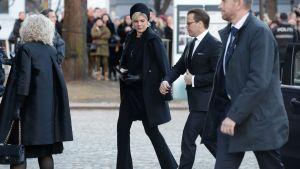 Tre svartklädda personer går på rad mot Ari Behns begravning.
