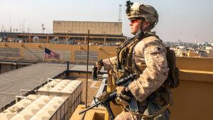 En amerikansk soldat vaktar en byggnad.