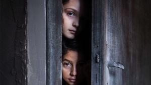 Kaksi tyttöä kurkistaa oven raosta.
