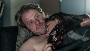 Mies ja nainen makaavat jossakin, nainen nojaten mieheen.