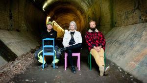 Kolme henkilöä istuu tuoleilla jonkinlaisessa tunnelissa.