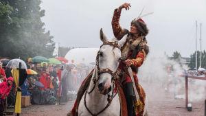 Keskiaikaiseen asuun pukeutunut nainen heilauttaa kättään valkoisen hevosen selässä. Taustalla savua ja yleisöä vesisateessa.