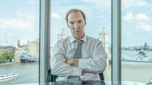 Mies kädet puuskassa jonkinlaisessa toimistohuoneessa, jossa taustalla isot ikkunat ja vesimaisema.