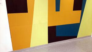 Rektangulära figurer i olika färger på en vägg.