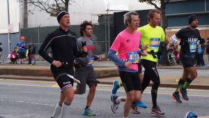 New York City Marathon 2014. En klunga på 5 människor springer i träningskläder på en gata. De har alla lappar med nummer på magen.