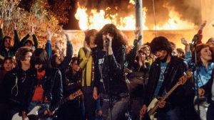 The Ramones soittaa, koululaiset riehuvat, koulu palaa taustalla. Kuva elokuvasta Rock 'n' Roll High School.