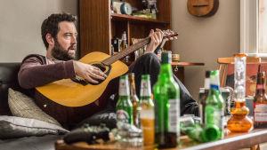 Mies istuu sohvalla ja soittaa kitaraa